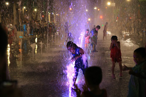 Trẻ em nô đùa với nước và ánh sáng.