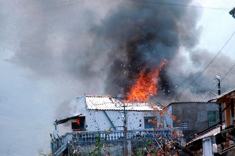 Một ngôi nhà bốc cháy do trúng đạn rocket. Ảnh: Angelo Cozzi/Getty.