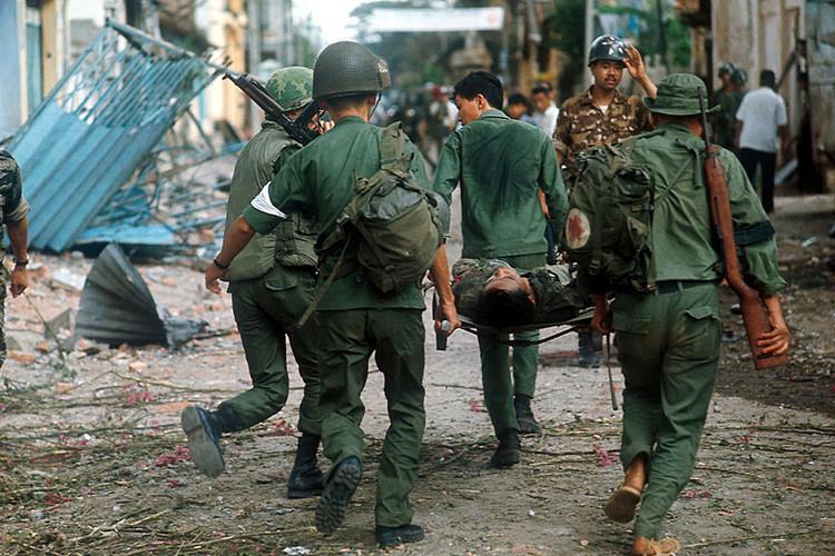 Binh sĩ chế độ Sài Gòn bị thương được đồng đội cáng trên đường phố. Ảnh: Angelo Cozzi/Getty.