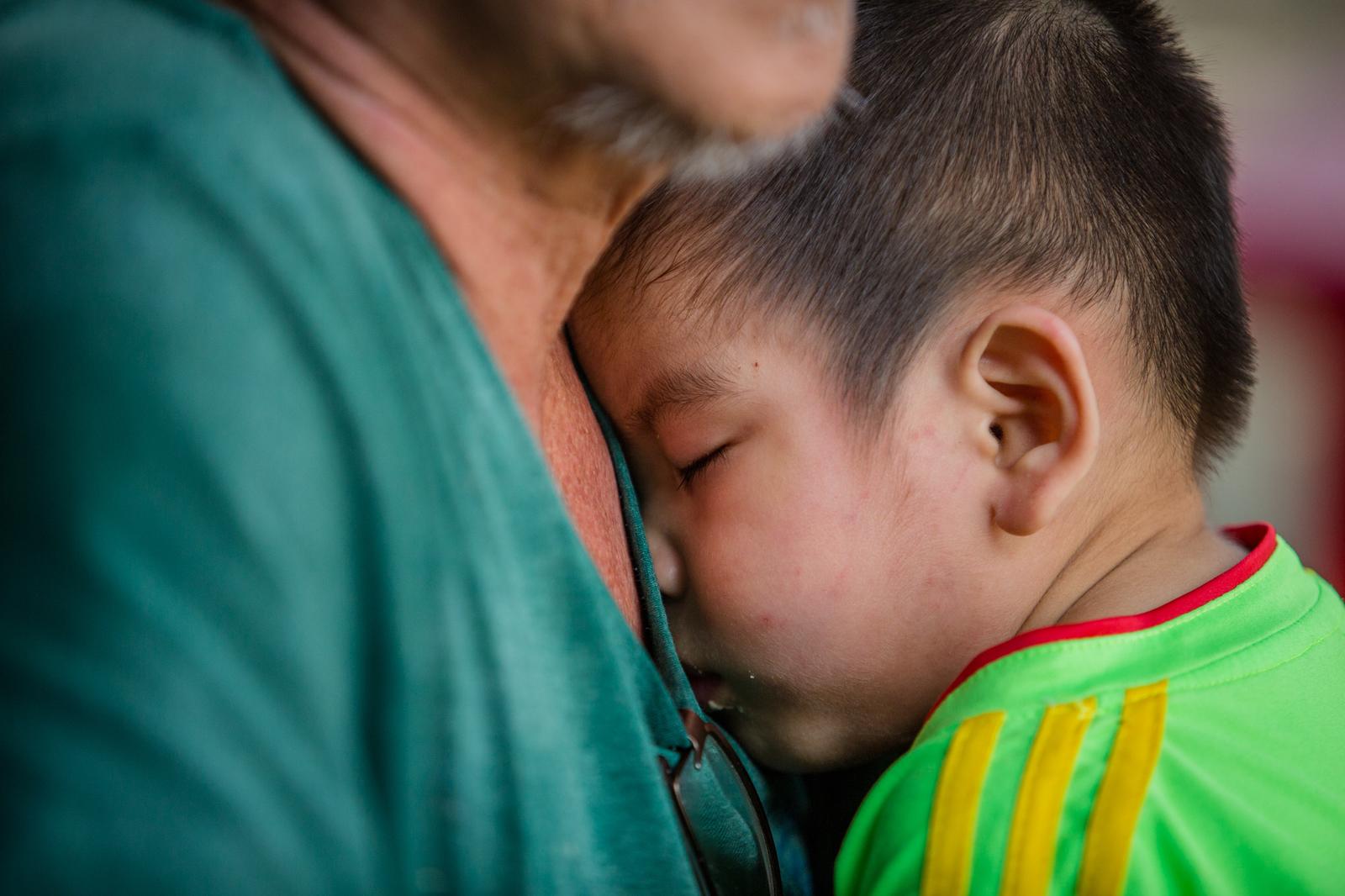 Một đứa trẻ ngủ trong lòng ông Hiệp - chủ mái ấm Thiên Thần