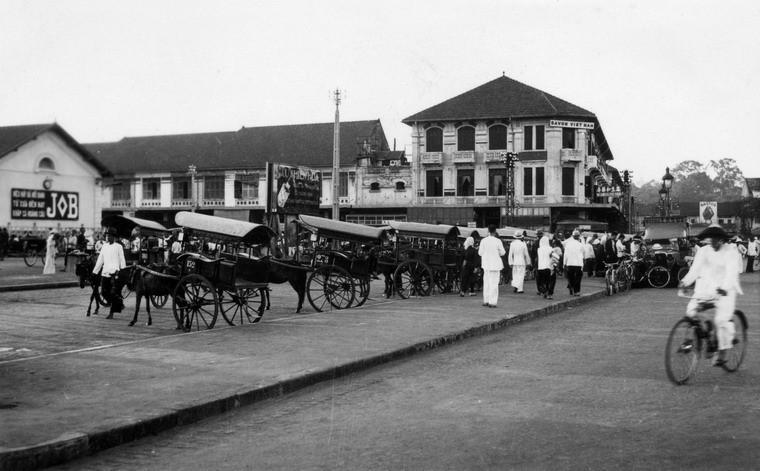 Từ kiểu xe ngựa sang trọng của Pháp, người Việt đã tạo ra loại xe ngựa đơn giản hơn với hai bánh, được gọi là xe thổ mộ. Trong ảnh là bến xe thổ mộ bên chợ Bến Thành, khoảng năm 1938-1939. Ảnh tư liệu.
