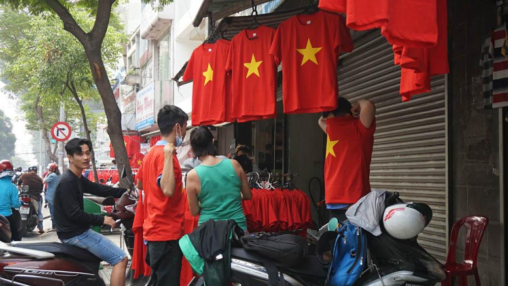 Nhiều người tập trung trước cửa hàng thời trang, chọn lựa áo cổ vũ tuyển U23 Việt Nam thi đấu