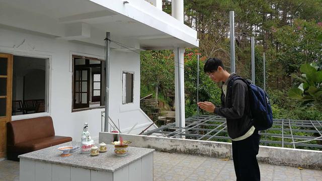 Một du khách thắp nhang tại ngôi nhà ma với thái độ kính cẩn - Ảnh: MAI VINH