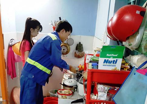 Vợ chồng anh Trương Trung Tín đang lọ mọ chuẩn bị cơm nước cho anh mang lên bến tàu ăn. Anh cho biết ăn cơm vợ nấu, vừa rẻ vừa ngon