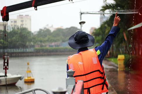 Lặng thầm giữa mưa nắng trên dòng kênh ở Sài Gòn 1 Anh Lương Anh Tuấn (tổ phó tổ vớt rác) đang đội mưa để chỉ dẫn cho tài xế lái xe cẩu đưa rác từ dưới ghe lên bờ