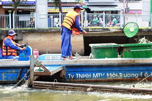 """Trên mỗi ghe vớt rác có 2 công nhân, người cầm lái, người kia có nhiệm vụ vớt rác """"kiêm"""" hướng dẫn hướng đi vì ghe tàu có thể va trúng các vật thể, gây hư hại"""