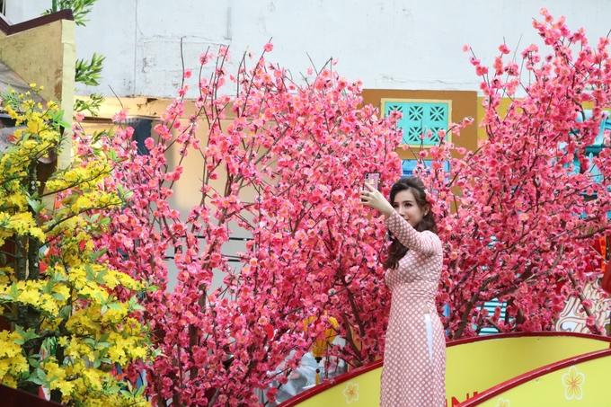 Mô hình dãy nhà màu vàng trông như phố cổ Hội An cũng được dựng gần đó. Không gian hoài cổ nên phố Ông Đồ trở thành điểm lý tưởng để chụp ảnh với áo dài truyền thống. Thiếu nữ đứng trên cầu, thích thú chụp ảnh với những cành đào hồng rực rỡ.