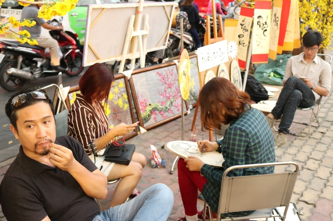 Bạn nữ kiên nhẫn ngồi chờ bức vẽ chân dung chính mình trong một quầy hàng trên lề đường.