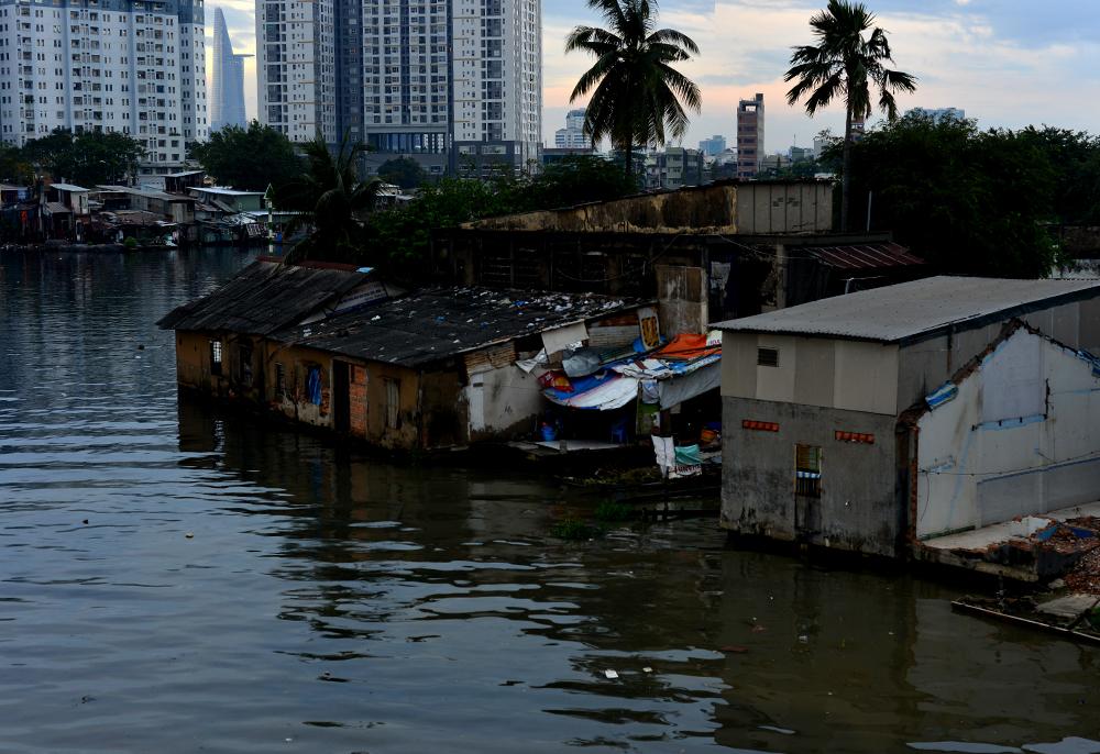 """Nhiều căn nhà tạm bợ nằm trên và ven kênh rạch là """"tồn tại của lịch sử phát triển đô thị trên địa bàn thành phố mấy chục năm qua""""."""
