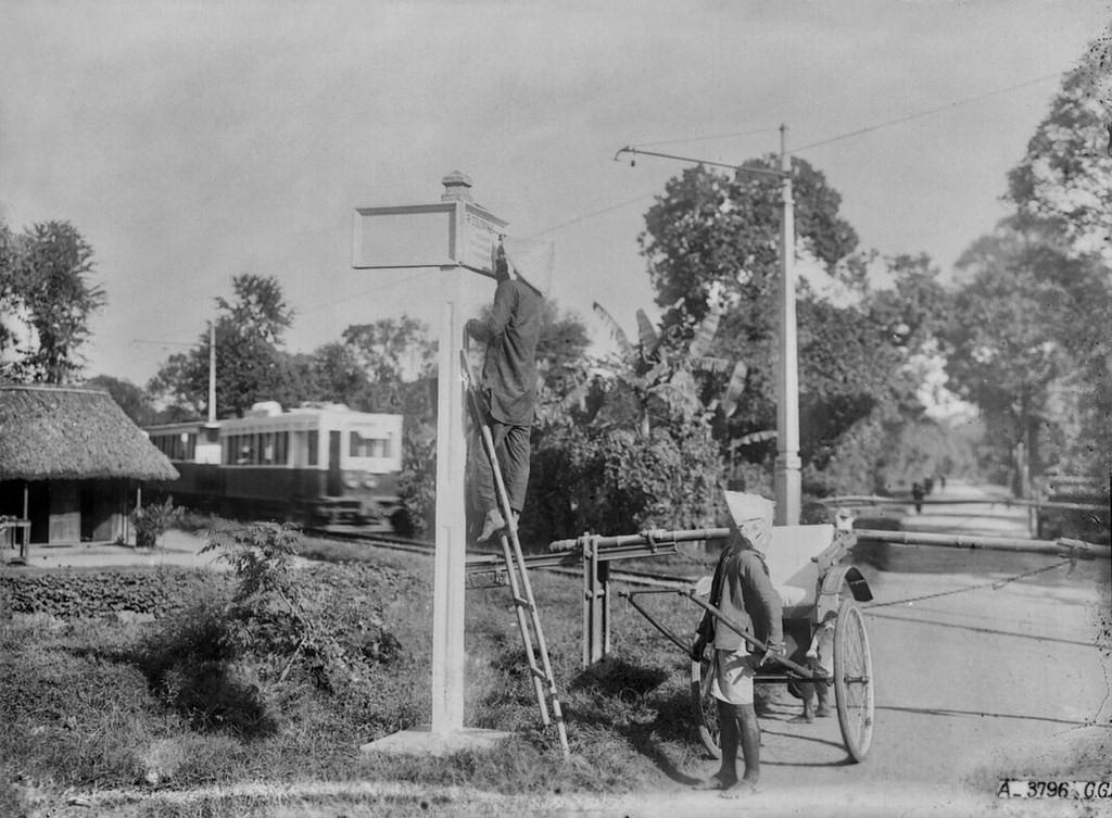 Người phu xe kéo xem người đàn ông đứng trên thang kẻ bảng tên đường trên đường Sài Gòn - Biên Hòa, thập niên 1920. Ảnh tư liệu.