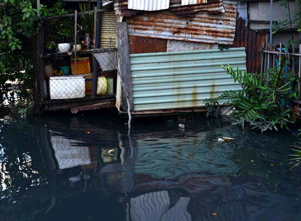 Nhiều căn nhà xập xệ lún sát xuống nước kênh đen, nhiều hôm triều cường lên nước dâng tràn vào cả trong nhà.