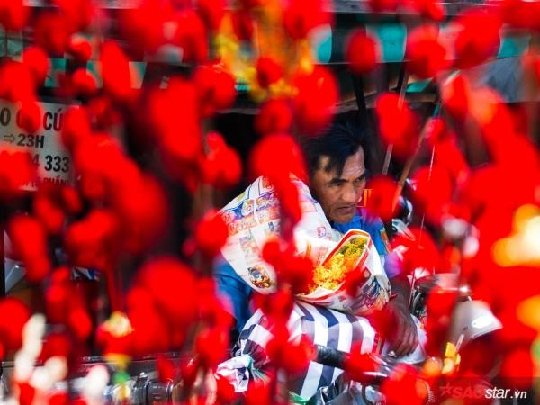 Sài Gòn hôm 30 Tết: Bác bảo vệ ở chợ hoa Hồ Thị Kỷ đang chen chân lựa cho mình bó vạn thọ tươi được bọc trong giấy báo gói ghém cận thận.