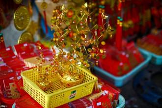 Bà Tiên bày bán mấy trăm mặt hàng khác nhau, từ những vật phẩm nhỏ có giá chỉ vài nghìn như bao lì xì, ngân lượng treo cành mai... cho đến đồng tiền loại đại có giá 500.000 đồng và đắt nhất là pháo điện, có giá từ 1 triệu đồng đến 1,5 triệu đồng. Trong ảnh, một cây vàng để bàn có giá 50.000-130.000 đồng, tuỳ theo kích cỡ.
