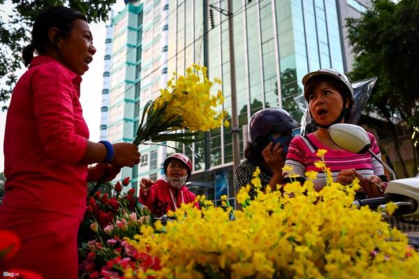 Bà Phạm Thị Yến Trinh (áo sọc hồng - trắng), một khách mua hoa tại hàng này nhận xét hoa nhựa do người bán tự kết vừa đẹp, bền lại rẻ. Bà vừa mua 4 bó hoa để trang trí.