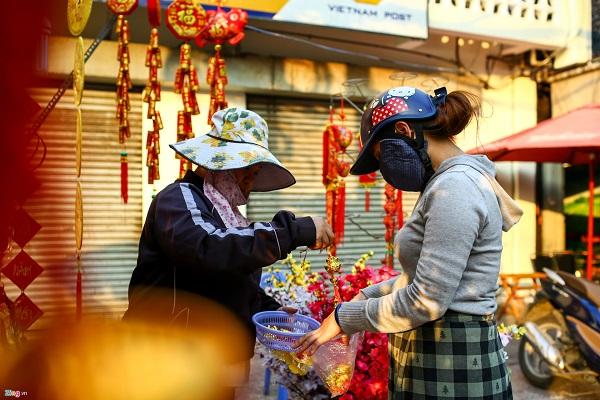 Chị Châu Thị Hồng Nhung (quận 10) đang mua những vật dụng để trang trí cây mai ngày Tết. Chị cho hay năm nào cũng từ nhà sang đây để mua hàng vì giá cả hợp lý. Hôm nay, chị chỉ mua 80.000 đồng.