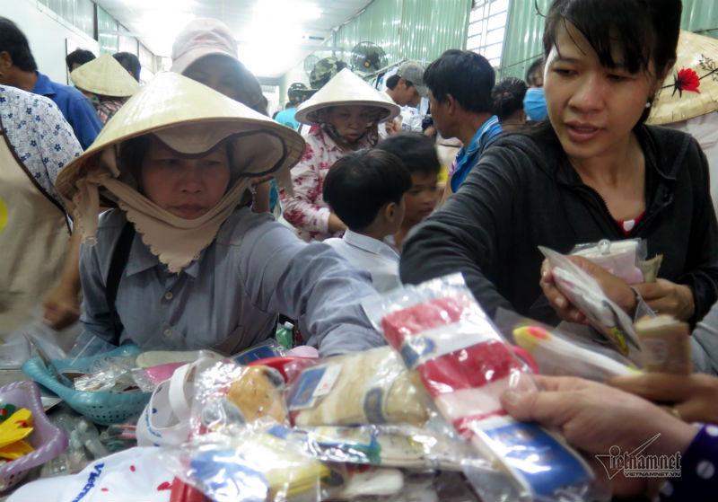 """Đi hai vòng chợ, chị Thu, quê Phú Yên (trái) bán vé số ở quận 7 đã tìm được món hàng cần mua. """"Mình tìm những gì mình cần mua thôi, còn để cho người khác nữa. Tôi mua ít đôi vớ để thay đổi khi đi làm cho tiện"""". – chị Thu nói."""