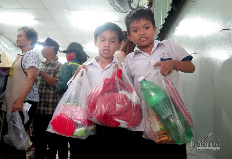 Em Quốc Đại (phải) HS lớp 3, trường Tiểu học Phú Mỹ, quận 7 sau giờ tan trường cùng mẹ đến phiên chợ mua hàng đồng giá.