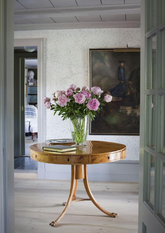 Lối vào nhà rộng rãi đủ để bạn đặt chiếc bàn tròn duyên dáng, đừng ngần ngại cắm thêm lọ hoa tươi. Không cần trang trí cầu kỳ vẫn giúp cho lối vào nhà thêm sức sống và sắc màu đón năm mới yên vui.