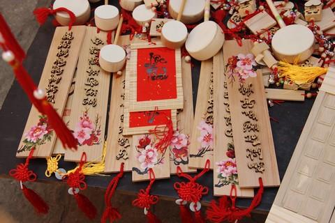 """Góc Phố ông đồ với đủ các kiểu loại nền chất liệu ghi chữ từ khắc gỗ, giấy lụa, giấy gió cho tới mành trúc, tre,.... Những câu sớ, con chữ tỏ ước mong một năm mới tốt đẹp với gia đình, người thân của người """"xin"""" chữ được viết ra bởi bàn tay của những ông đồ."""