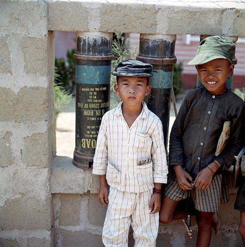 Hai cậu bé đứng cạnh một bức tường được dựng bằng vỏ bình xăng Mỹ. Ảnh: Geheugenvannederland.nl