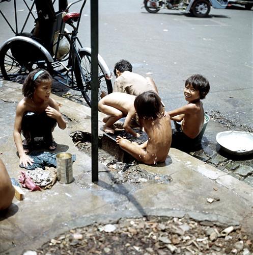 Trẻ em tắm giặt trên hè phố Sài Gòn. Ảnh: Geheugenvannederland.nl