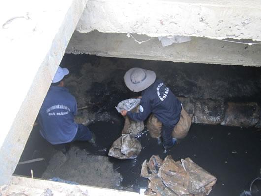Những ống cống phi 2.000 thì có thể đi bộ trong đó để cào bùn, còn ống nhỏ hơn thì phải chui, lặn ngụp dưới nước thải mới cào được – anh Nguyễn Văn Giàu nói với PV Infonet khi đang múc bùn, rác ở đường Nguyễn Văn Quá (Q.12). Trong ảnh, đội công nhân của Cty thoát nước và xử lý nước thải Đà Nẵng đang gắng làm xong phần việc trong cống ngầm trên đường Mai Am, Q.Hải Châu, tháng 8/2015. (Ảnh: cadn.com.vn)