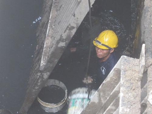 Rác bùn múc lên được chuyển vào thanh móc để đồng nghiệp bên trên kéo lên. Người công nhân sẽ ngâm cả người trong cống nước như thế cho tới khi lòng cống được nạo vét xong. (Ảnh: nld.com.vn)