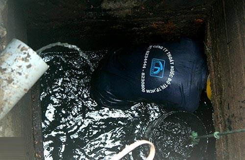 Chui ngập đầu vào ống cống để vét bùn. Nước thải ở trên vẫn tiếp tục chảy vào cống. (Ảnh: khampha.vn)