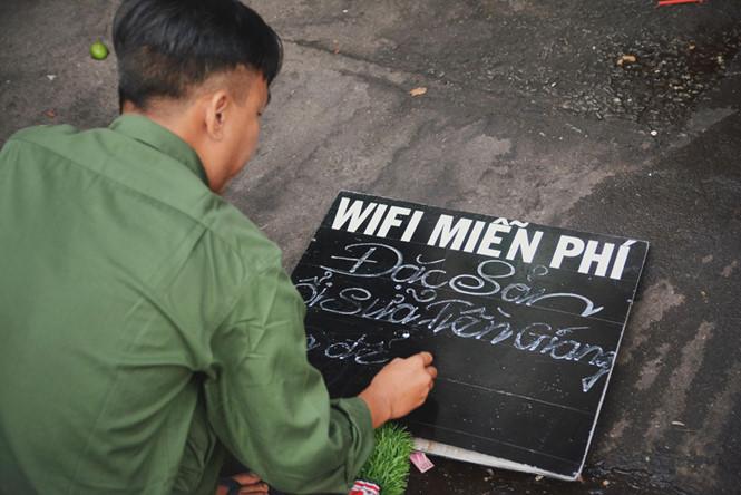 Anh Hiển nắn nót từng dòng chữ trên tấm bảng hiệu. Chữ anh đẹp và những câu slogan bán hàng thì vô cùng ngộ nghĩnh.