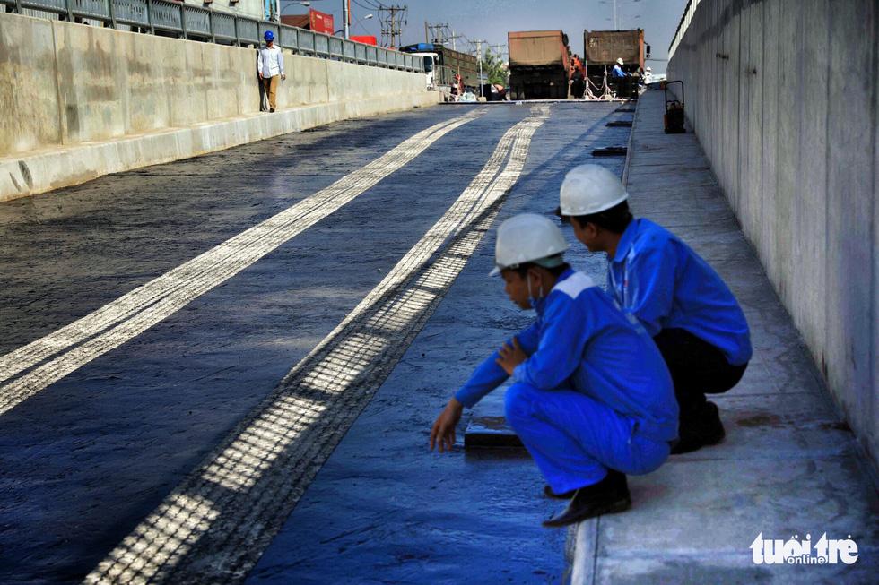 Công tác trải nhựa đường được kiểm tra kỹ để giữ độ bền trong mặt hầm với chiều rộng từ 9-9,5m cho hai làn xe lưu thông - Ảnh: HỮU KHOA