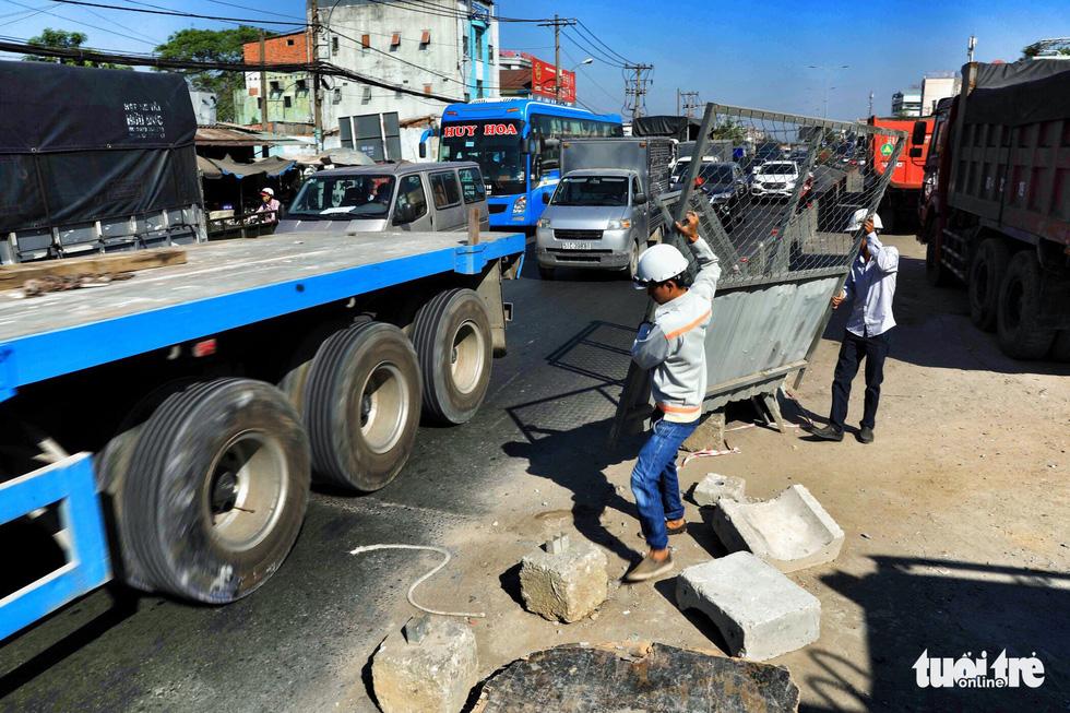 Dọn dẹp các lô cốt bên ngoài đường hầm chui cho xe thuận tiện lưu thông - Ảnh: HỮU KHOA