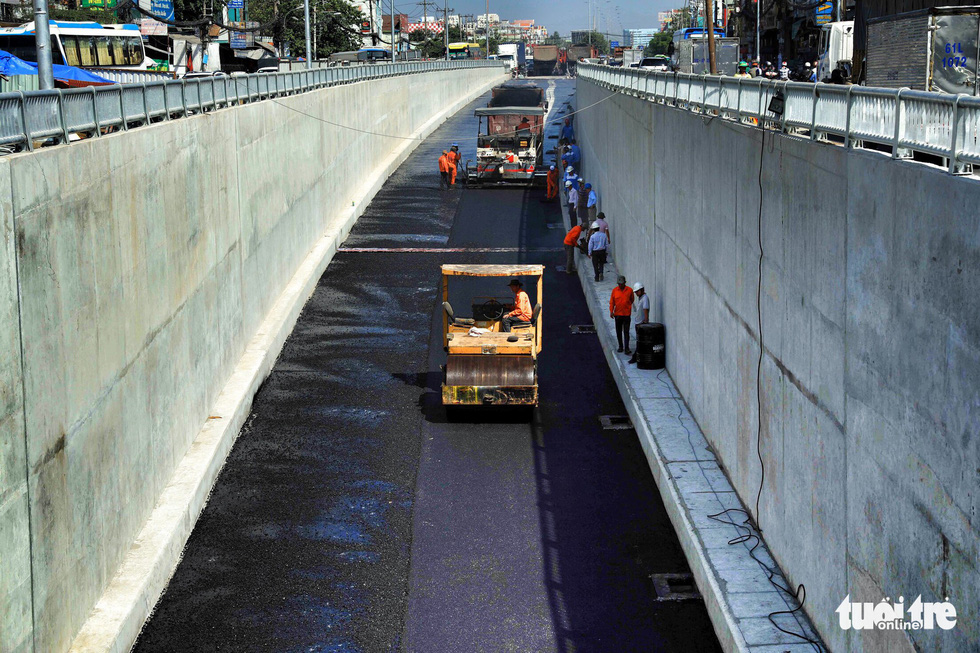 Tất bật thi công phần nhựa đường cho mặt hầm chui phía quốc lộ 22 dài 180m - Ảnh: HỮU KHOA