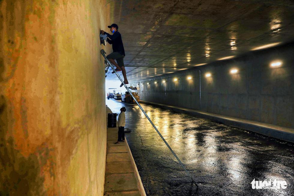 Lắp đặt hệ thống đèn led chiếu sáng trong đoạn hầm kín chui qua vòng xoay An Sương dài 125m - Ảnh: HỮU KHOA