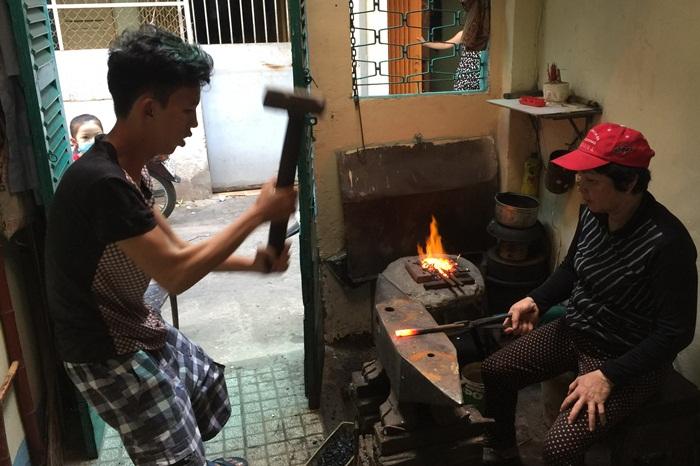 Vinh, con trai chị Nguyệt, đang giúp mẹ