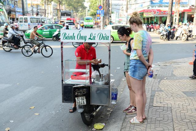 Khách nước ngoài thích thú món ăn đường phố TP.HCM - Ảnh: QUANG ĐỊNH