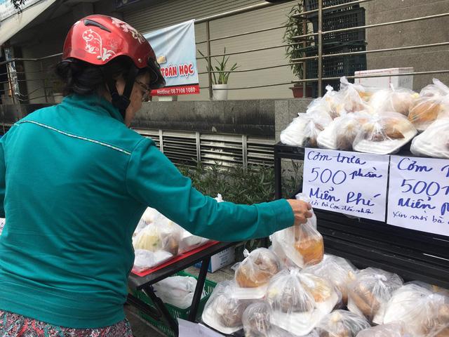 Một phụ nữ đến lấy cơm miễn phí - Ảnh: UYÊN TRINH