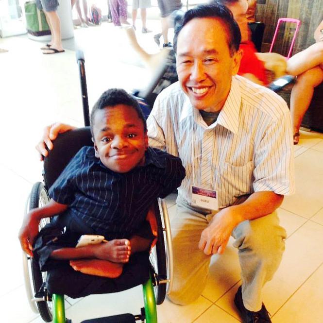 Ông Tôn Thất Hưng trong một chuyến đi công tác, chụp ảnh bên cạnh người khuyết tật ẢNH: NVCC