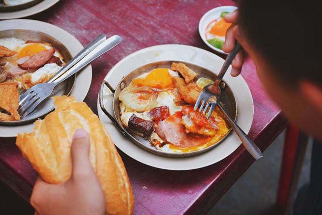 Chiếc chảo nhỏ bốc khói đầy bắt mắt với màu nâu của thịt nguội, đỏ hồng của xúc xích cháy cạnh, màu vàng của trứng chiên… Cạnh bên là ổ bánh mì to tròn, nóng giòn, ăn kèm cùng một dĩa đồ chua xắt lát.