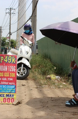 Giữa cái nắng đổ lửa của Sài Gòn, mái che của cô bạn Thu Hà chỉ là một cây dù.