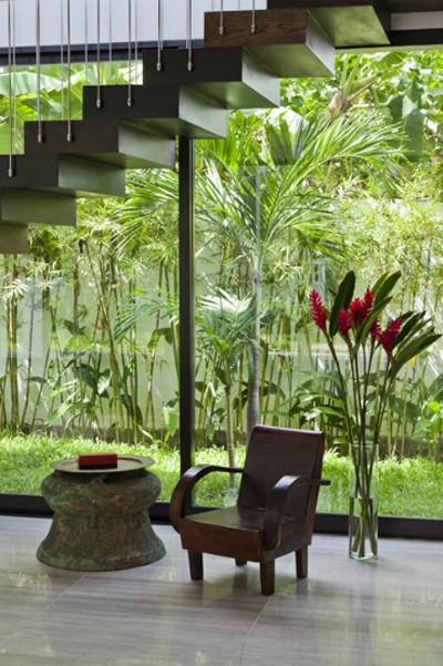 Các bậc thang thiết kế thanh mảnh cùng khoảng vườn cây xanh trong ngôi nhà ở Sài Gòn tạo thành một không gian thoáng rộng dưới cầu thang. Góc thư giãn nhiều cảm xúc hơn nhờ sự xuất hiện của chiếc ghế quen thuộc với nhiều gia đình trước đây và chiếc trồng đồng, mâm đồng làm bàn trà.