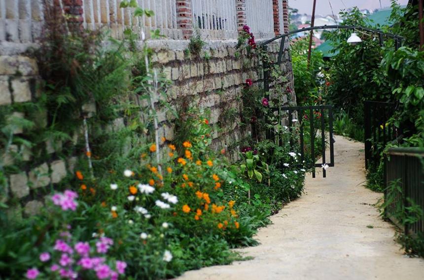 """Nằm nép mình giữa không gian chỉ toàn đồi núi, cây cỏ, Jang & Min hiện ra như ngôi nhà nhỏ trên thảo nguyên. Ngôi nhà ấy có lối vào phủ đầy hoa, có cánh cổng màu xanh cao chưa quá đầu, có view ngắm hoàng hôn và bình minh đẹp """"quên sầu"""". Những chi tiết nhỏ trong nhà đều được thiết kế xinh xắn. Ảnh: Jang & Min's house."""