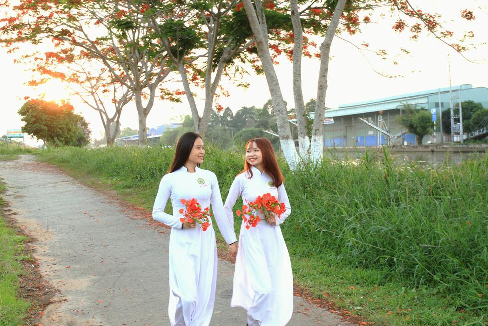 Nguyễn Thị Minh Thu, học sinh lớp 12D4 Trường THPT Lấp Vò 1, Đồng Tháp (phải), cùng bạn chụp ảnh ở con đường hoa phượng - Ảnh: HOÀNG PHÁT