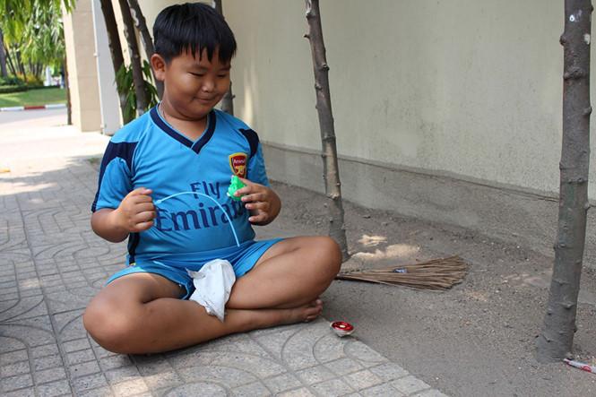 Cậu bé chơi đùa với món đồ chơi duy nhất của mình
