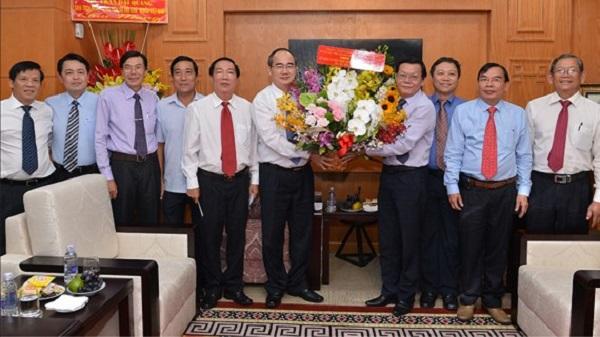 Bí thư Thành ủy TPHCM Nguyễn Thiện Nhân chúc mừng các nhà báo. Ảnh: SGGP