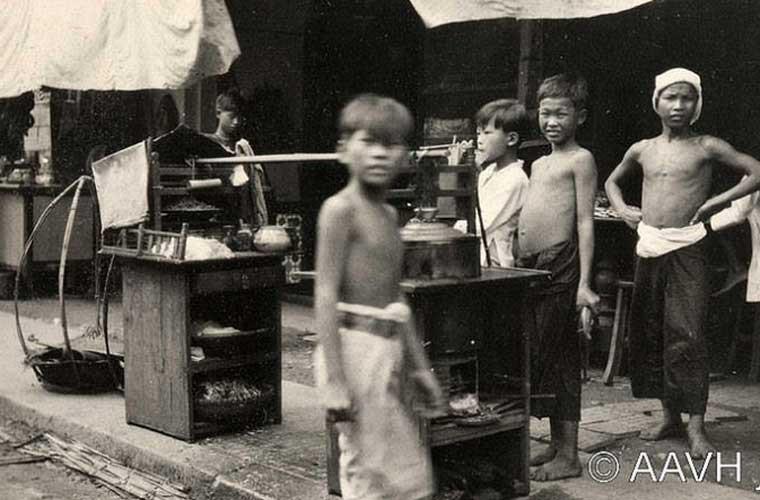 Theo Wikipedia, Chợ Lớn (với tên Hán Việt là Đê Ngạn) là khu vực đất rộng lớn với đông đúc người Hoa sinh sống nằm ở ven con kênh Tẻ trải dài suốt từ Quận 5 và Quận 6. Trong giai đoạn những năm 1930-1950, Sài Gòn và Chợ Lớn chính thức sáp nhập với nhau. Ảnh: Các bé trai đứng gần một gánh tào phớ tại khu chợ buôn bán ở Chợ Lớn.