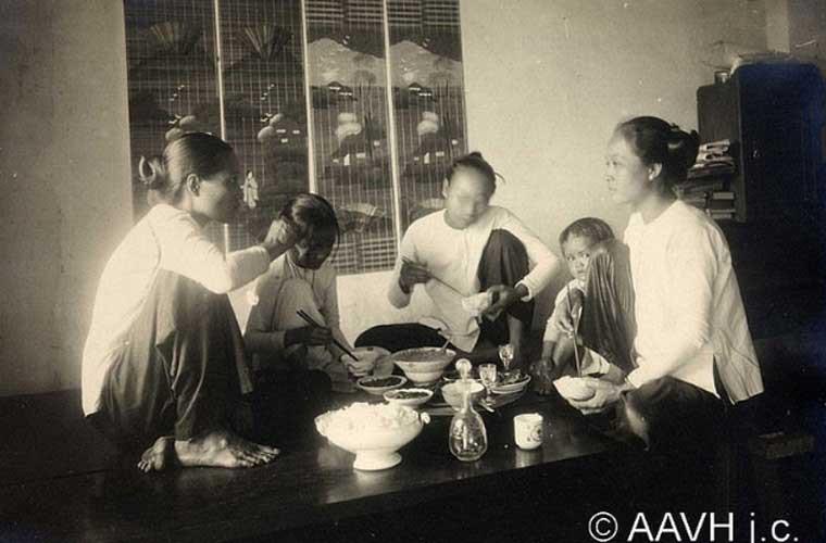Một gia đình đang quây quần ngồi ăn bên nhau. Ảnh chụp ở khu Chợ Lớn năm 1925.