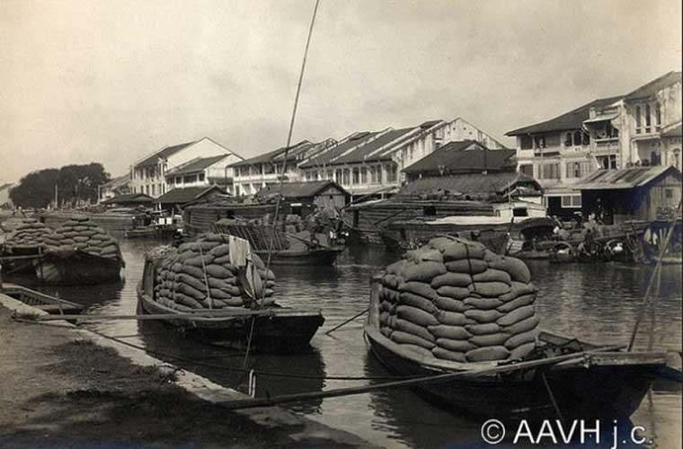 Thuyền chở đầy các bao gạo đang chờ xuất bến trên con kênh ở Chợ Lớn.