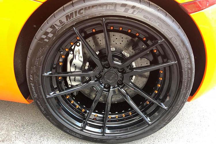 Về nguyên bản McLaren 650S Spider có bộ mâm 5 cánh kép nguyên bản màu xám khói 20 inch đẹp mắt, nhưng ở chiếc xe trong bài viết này nó đã được thay thế bằng mâm của hãng ADV.1 với thiết kế 5 chấu kép sơn đen với điểm nhấn là vành trong với những con ốc màu cam nổi bật.