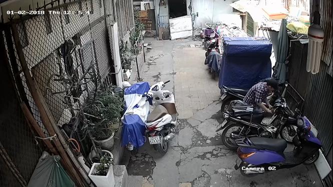 Một tên trộm đang bẻ khóa xe máy đậu trong hẻm bị một camera an ninh ghi lại.