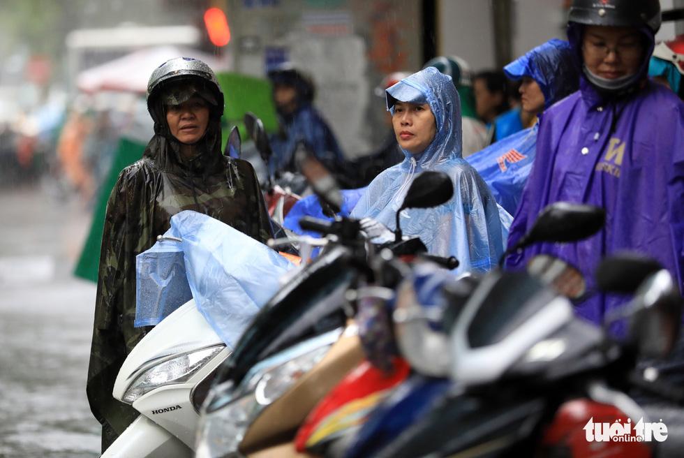 Không ngại mưa gió các phụ huynh với tâm trạng hồi hộp chờ con - Ảnh: HỮU KHOA